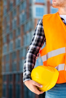 Close-up construction engineer holding helmet
