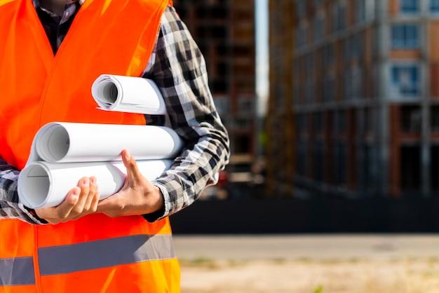 Крупным планом инженер-строитель держит в руках планы