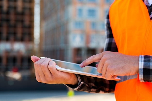 Close-up construction engineer using tablet