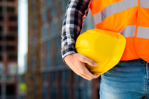 Close-up construction worker holding helmet