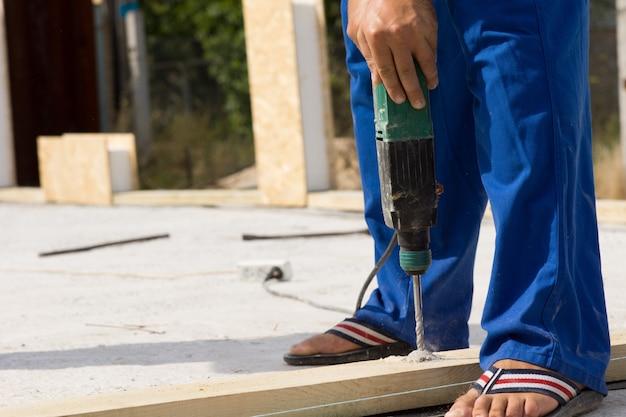 Закройте вверх строителя использовать сверло в строительстве дома недвижимости.
