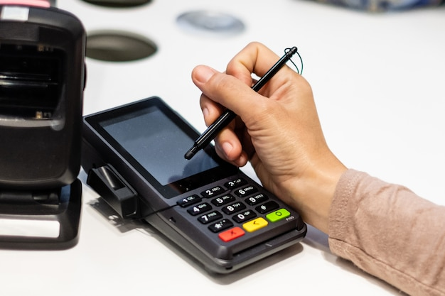 Close-up of consumer's hand signing on a touch screen of credit card sale transaction receipt machine.