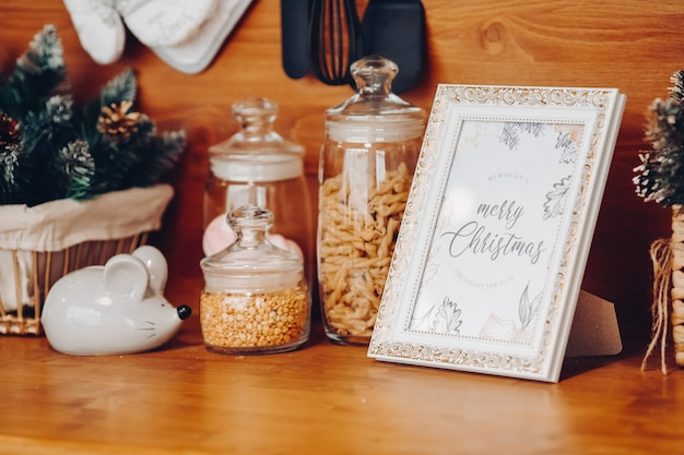 Close-up of containers of cereals, salt cellar in shape of new year s symbol mouse and photo frame with merry christmas text.