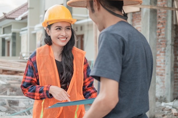 Close up of contractor smiling to builder in building construction background
