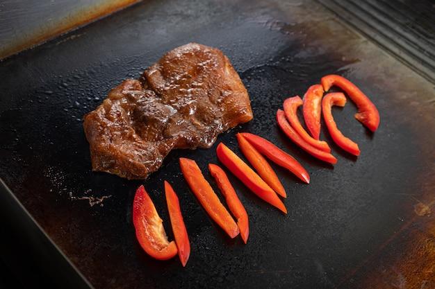 Крупным планом повар жарит на большой профессиональной плите большой маринованный кусочек мяса и перца. процесс жарки мяса