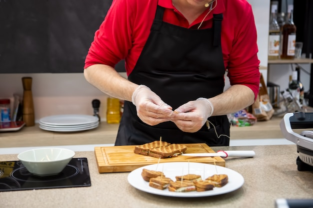 Close up of cook man in rubber gloves prepare snacks grilled sandwiches. soft focus, background is kitchen in blur