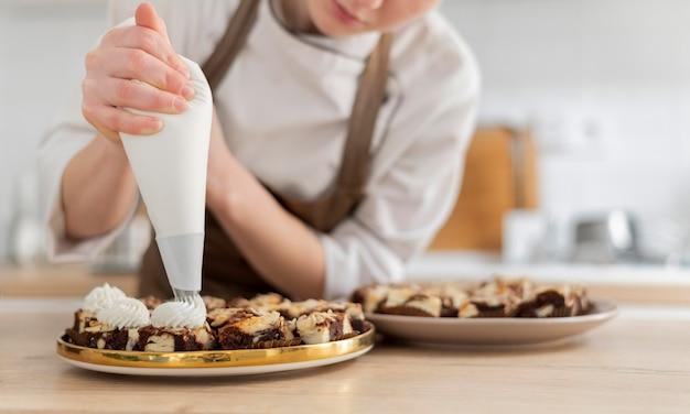 Chiuda sul cuoco che prepara il dessert