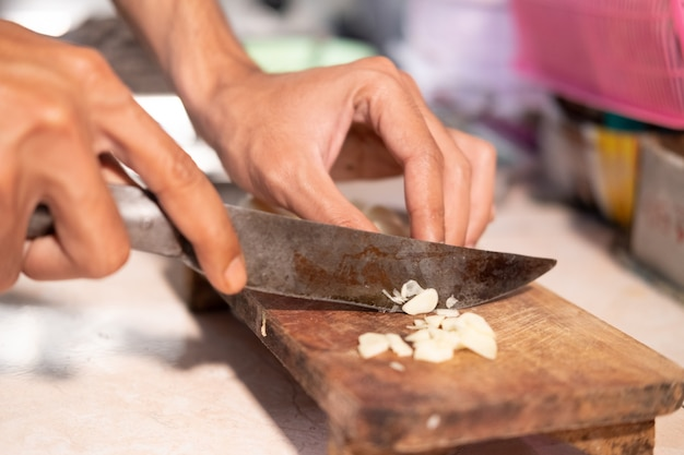 Close up of the cook's hand while slicing garlic with a knife and wooden cutting board
