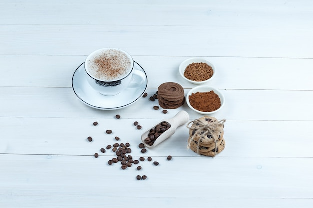 Close-up cookies, cup of coffee with bowl of instant coffee, coffee beans, cinnamon on white wooden board background. horizontal