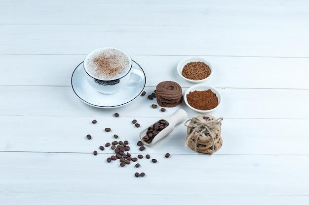 クローズアップクッキー、インスタントコーヒーのボウルとコーヒー、コーヒー豆、白い木の板の背景にシナモン。水平