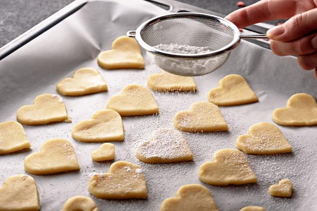 ベーキングシートのパーチメント紙にクッキーのハートをクローズアップストレーナーを通して上に粉砂糖を振りかける