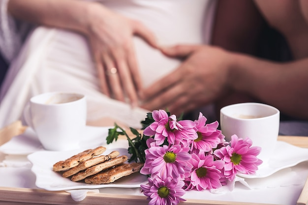 Close-up cookies on a plate and a bouquet of flowers on a background of heart on a pregnant belly.