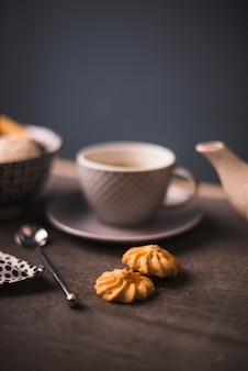 Close-up of cookies on table with tea cup in background