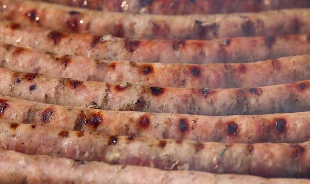그릴에서 고기 소시지 요리를 닫고, 흡연하고 굽고, 높은 각도 보기
