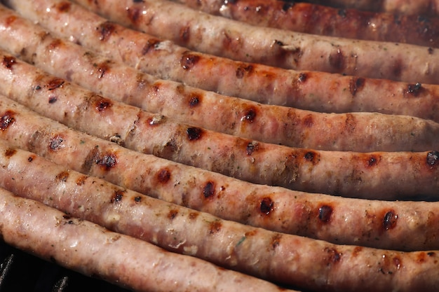 グリルで肉ソーセージを調理し、それらを喫煙して焼く、高角度のビューをクローズアップ