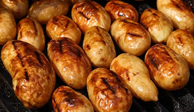 주철 금속 화격자가 있는 야외 숯불 그릴에서 감자 요리를 닫습니다