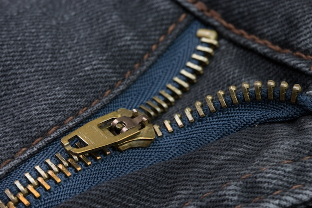 Close-up of a copper color zipper with black jeans