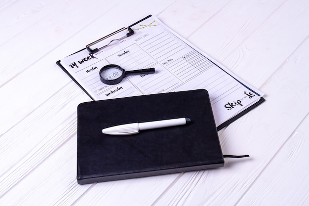 Close-up copybook with white pen and week calendar. white desk background.