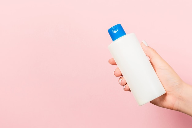 Close up of cosmetics bottle in female hand at pink background