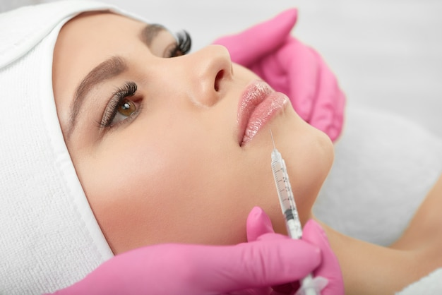 Close up of cosmetological lips enlargment process.