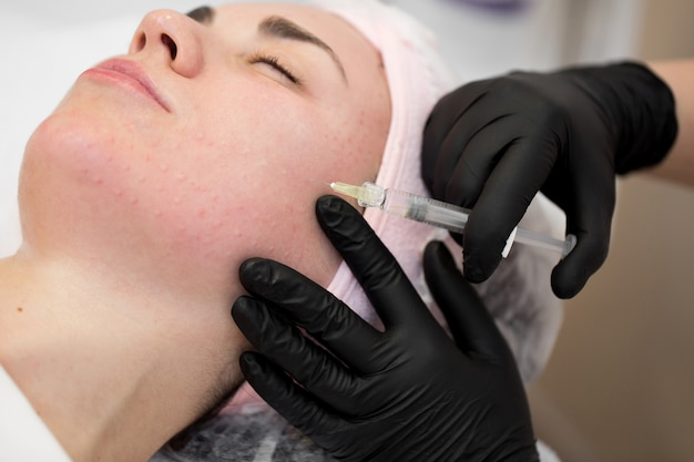 Close-up of cosmetologist makes the rejuvenating facial injections procedure for tightening on the face skin of woman in a beauty clinic.