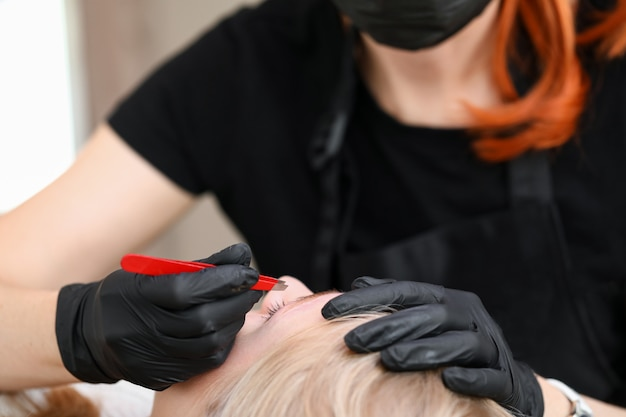 Close-up of cosmetologist wearing gloves and pluck eyebrows with tweezers. salon worker preparing womans brows for permanent makeup. mua and beauty treatment concept