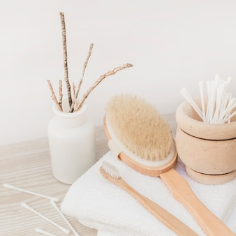 Close-up of cotton swab; towel and brush on wooden surface