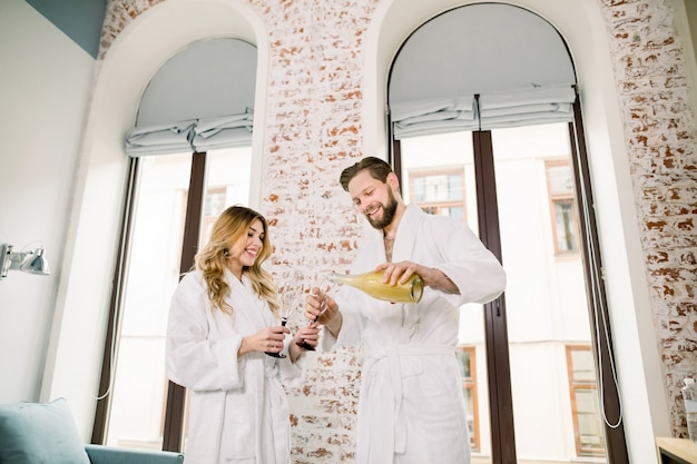 Close-up of a couple drinking champagne in hotel room. handsome man pours champagne in glasses