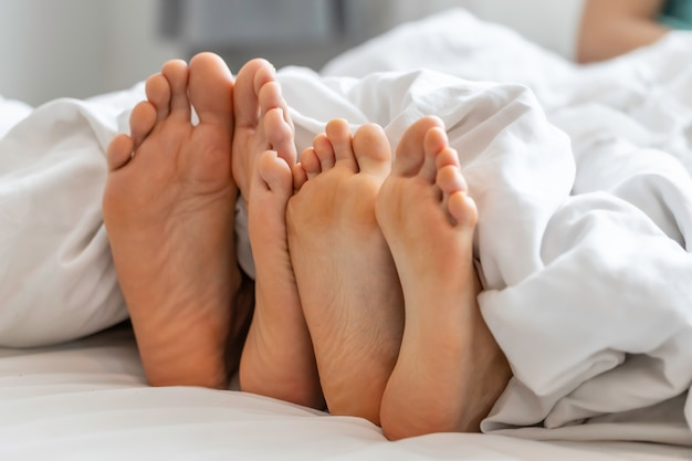 Close up couple of feet in a bed.