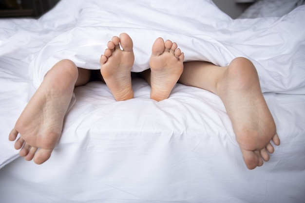 Close-up on couple feet having sex under the bed blanket