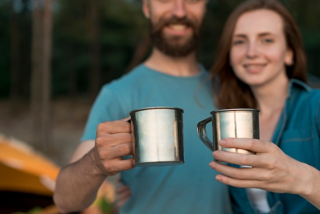 Close up couple holding drinking cups