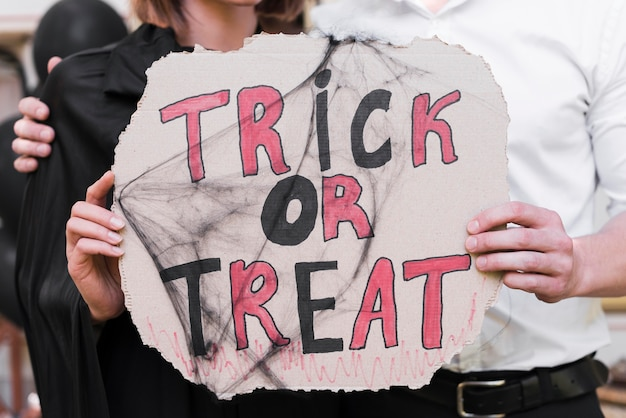 Close-up couple holding halloween sign
