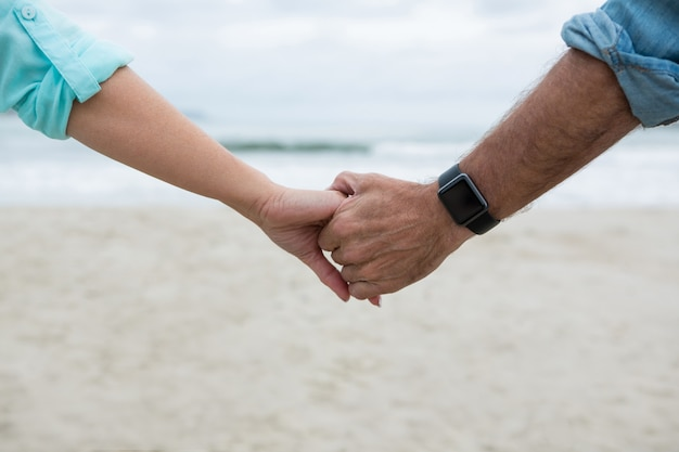 Close-up of couple holding hands on beach