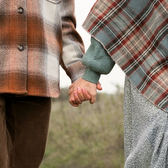 Close-up couple holding hands in nature