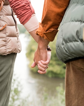 Close-up couple holding hands near river