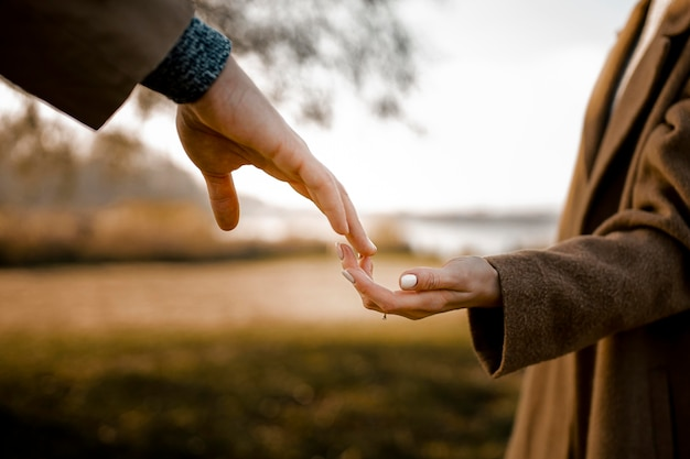 Close-up couple holding hands outdoors