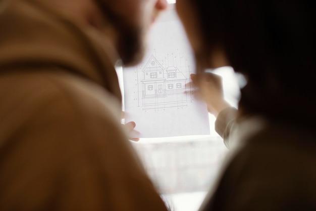 家の計画を保持しているカップルをクローズアップ