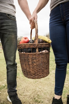 Close-up of couple holding picnic basket full of fruits