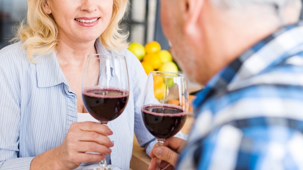 Close-up of couple holding wineglasses in hand