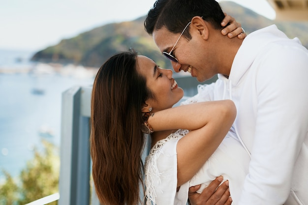 Close up couple hugging on the balcony with ocean view, indian brunette guy hug asian girl in white clothing.