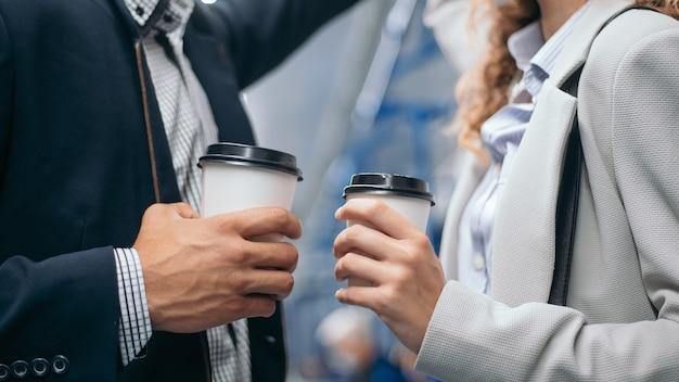 閉じる。地下鉄の車に立っている間、持ち帰り用のコーヒーに恋をしているカップル。