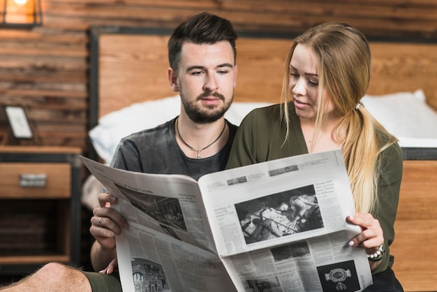 Close-up of couple looking at newspaper