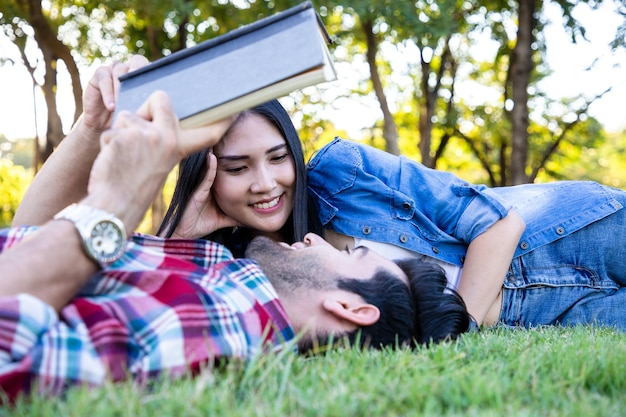 Close up of couple love consultant and reading book projects with bright smile in public park they rest after hard learning by relax and leisure on green grass spring season