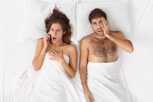 Close up on couple lying in bed under white blanket