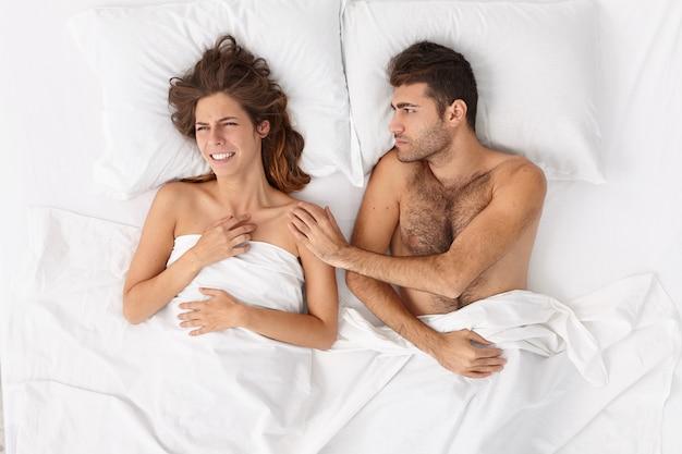 Primo piano sulla coppia sdraiata a letto sotto il manto bianco
