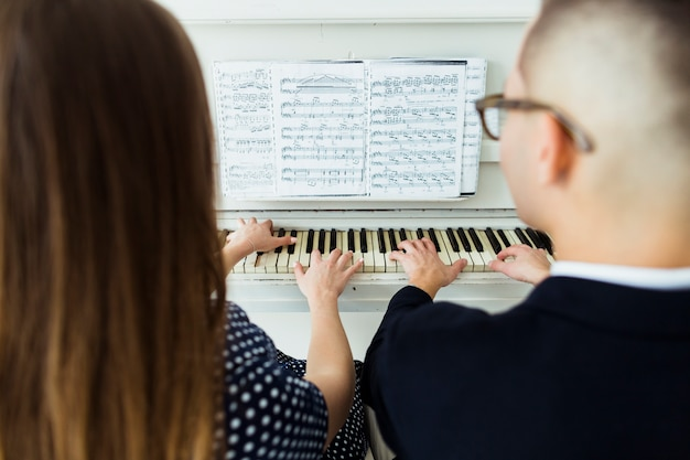 Close-up of couple playing piano with musical sheet