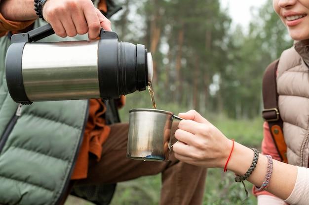 Крупным планом пара наливает горячий напиток на природе