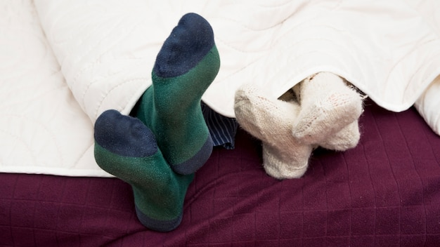 Close-up of couple's foots under cover in a bed