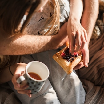 Close-up of couple's hand holding baked pastry and coffee cup