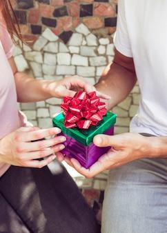 Primo piano del contenitore di regalo della holding della mano di una coppia